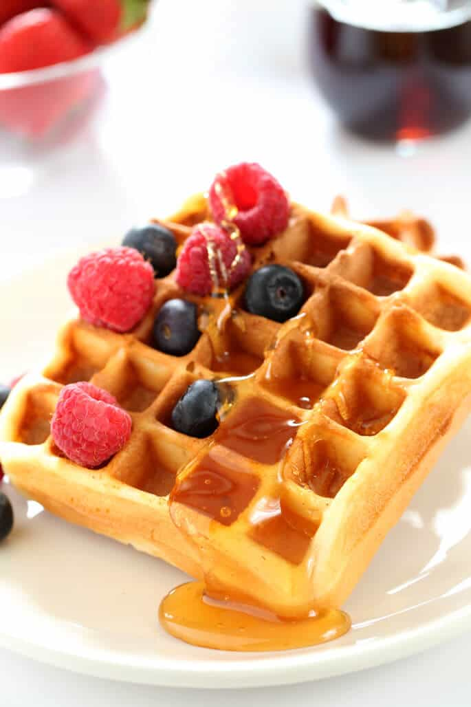A close up of a waffle with raspberries, blueberries and syrup