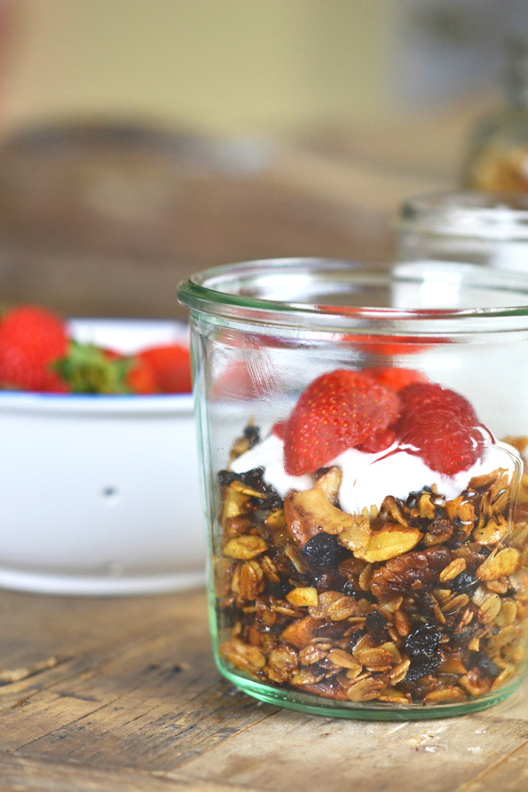A jar with granola and whip cream and strawberries