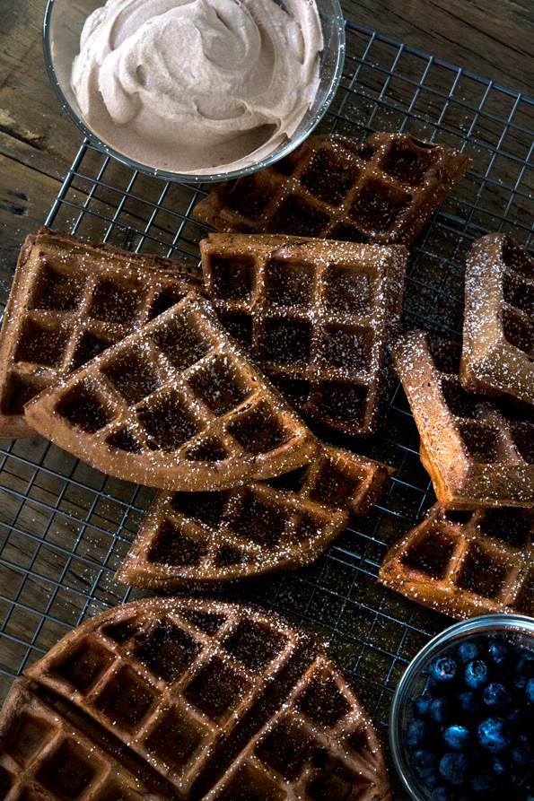 Overhead view of chocolate waffles on black tray