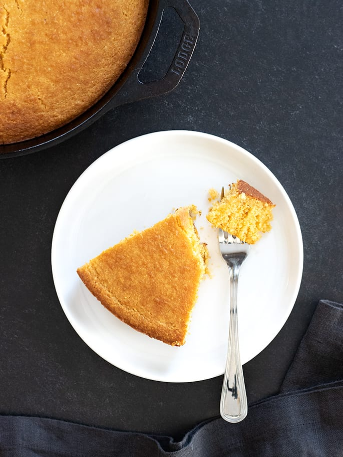 Old fashioned gluten free cornbread corn flour variation, slice on plate with forkful.