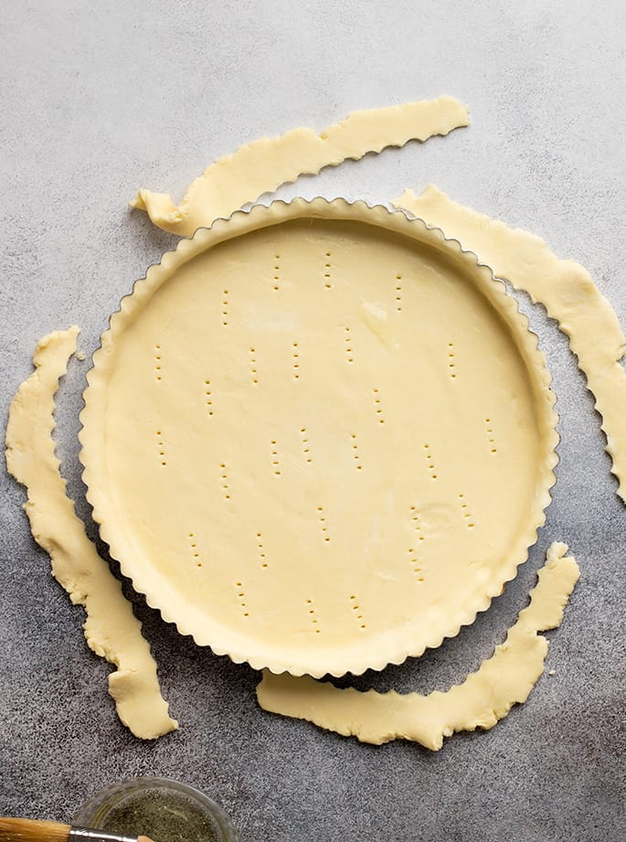 Overhead image of raw tart crust in pan with scraps on sides of pan