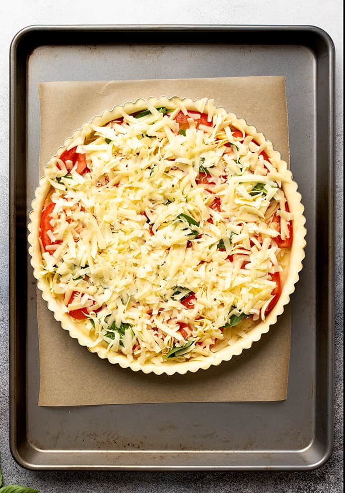 Overhead image of unbaked tomato tart on brown paper on metal baking sheet