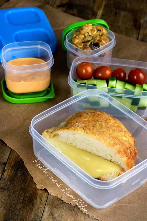 A plastic container filled with a sandwich and vegetables