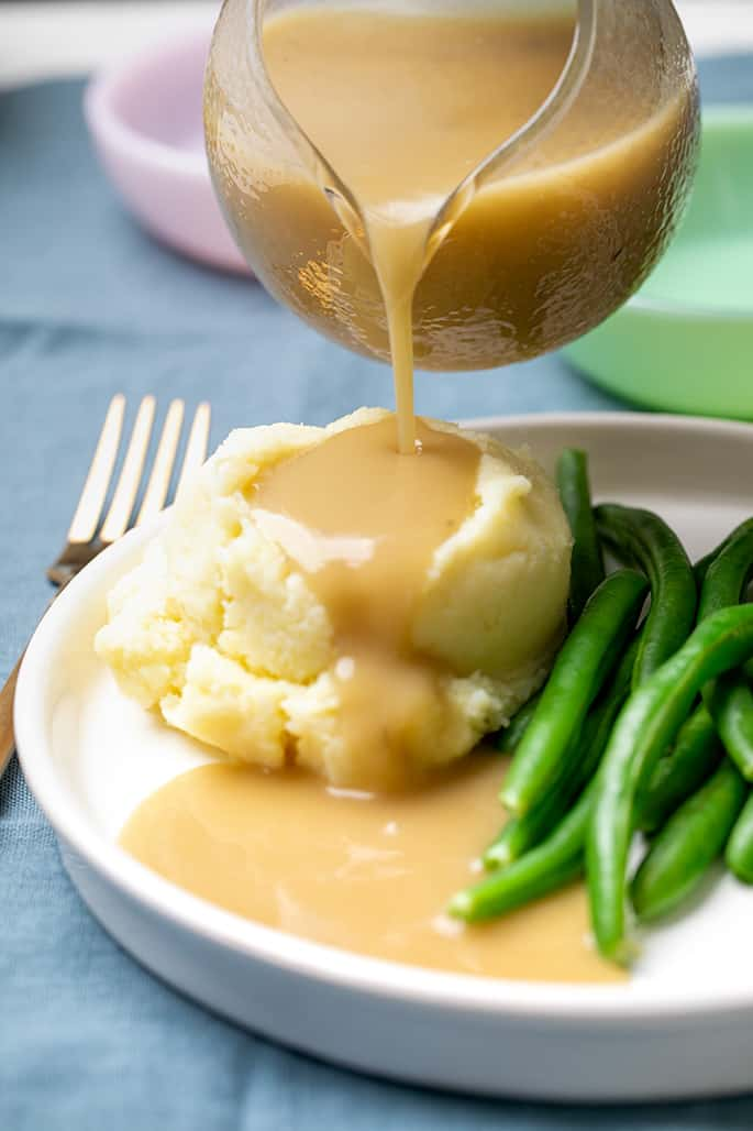 Gravy boat pouring gravy onto mashed potatoes with string beans on white plate on blue cloth with more dishes in background