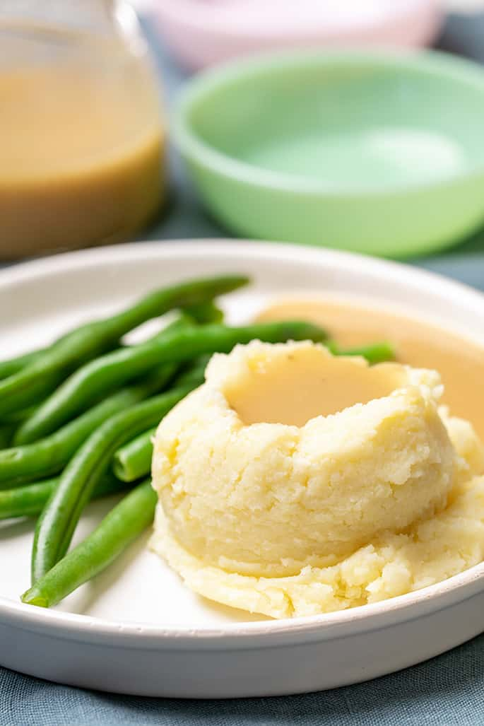 Gravy on mashed potatoes with green beans on white plate with dishes in background
