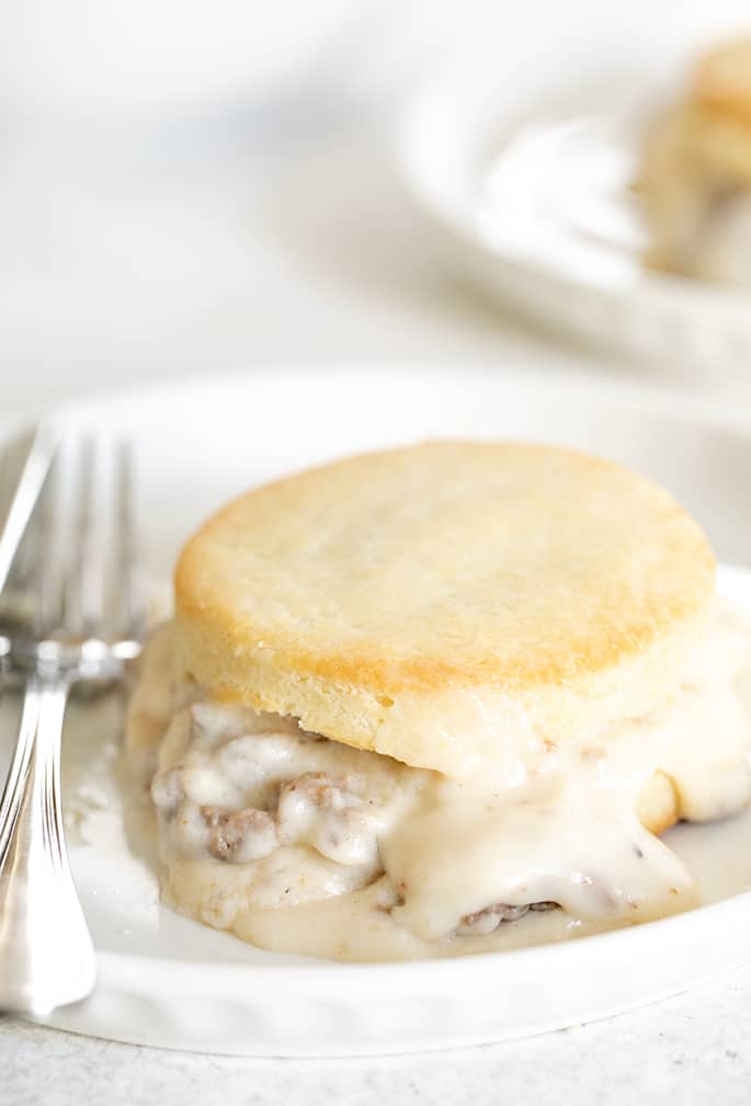 Sausage gravy on a biscuit on a plate with a fork closeup image