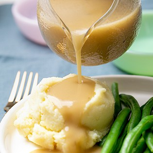 Small square image of gravy boat pouring gravy onto mashed potatoes with string beans on white plate