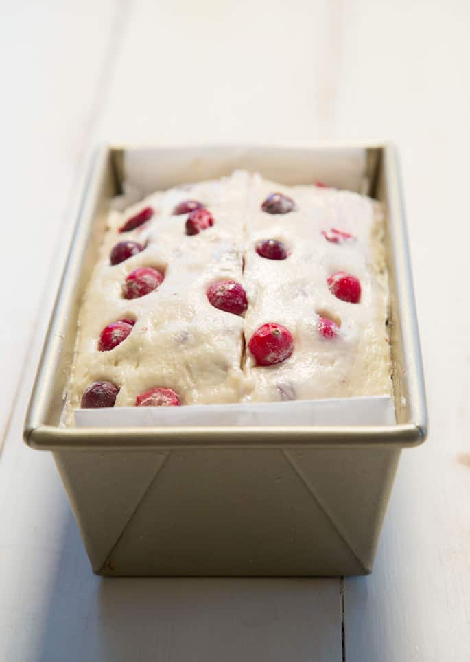 A loaf pan with the cranberry bread dough inside