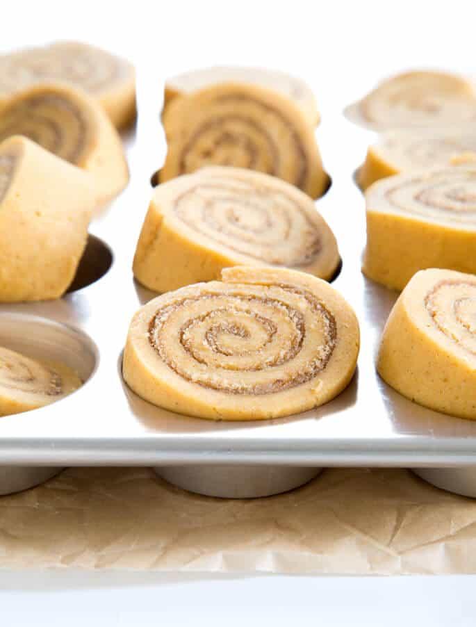 raw shaped pumpkin cinnamon rolls in metal muffin tray
