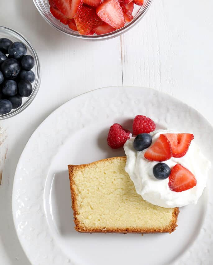 Overhead view of pound cake, whip cream and fruit on a white plate