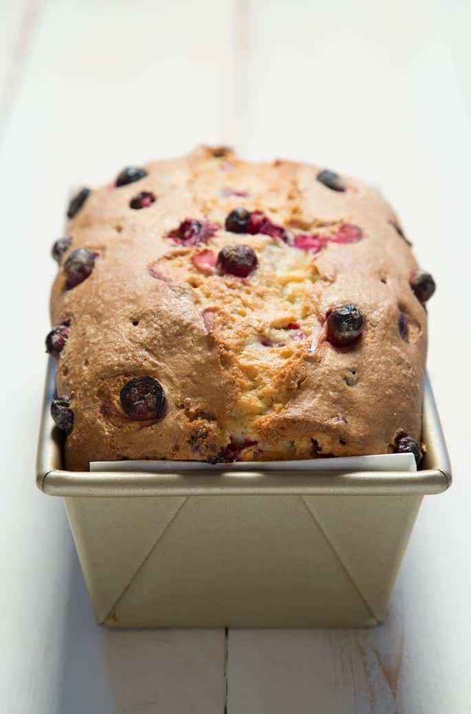 A close up of the top of the cranberry bread in a loaf pan.