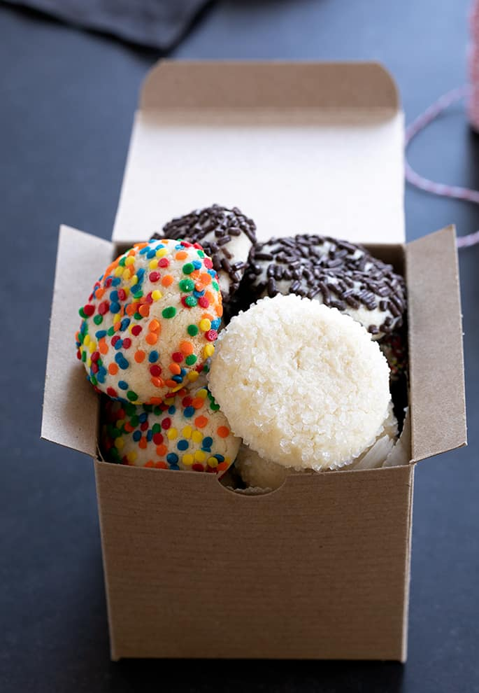 A box of drop sugar cookies with different toppings