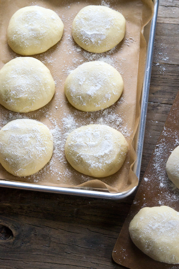 Image from above of raw gluten free Hawaiian bread rolls rising on a tray.