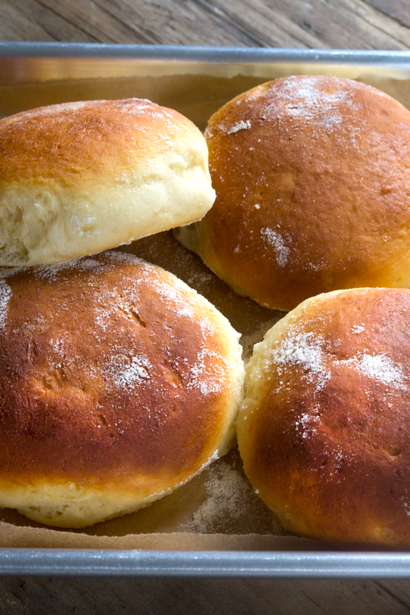 A close up of a gluten free Hawaiian bread rolls in a pile on a tray.