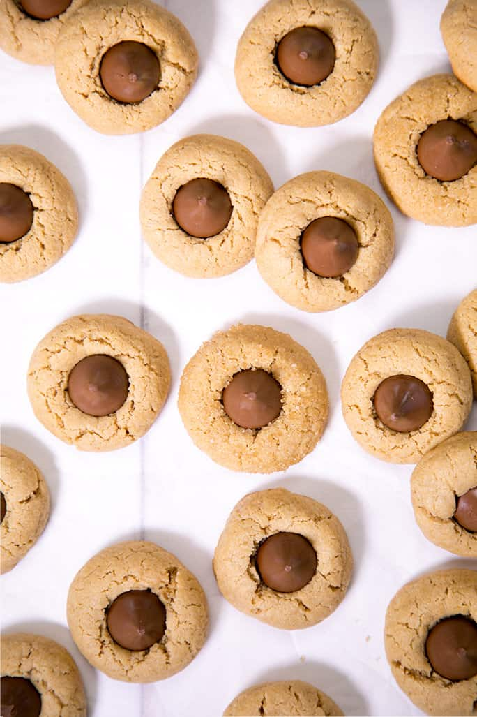 Birds eye view of peanut butter blossom cookies on white surface