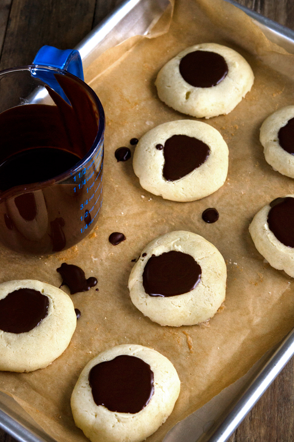 Overhead view of thumbprint cookies with chocolate on top on a brown surface