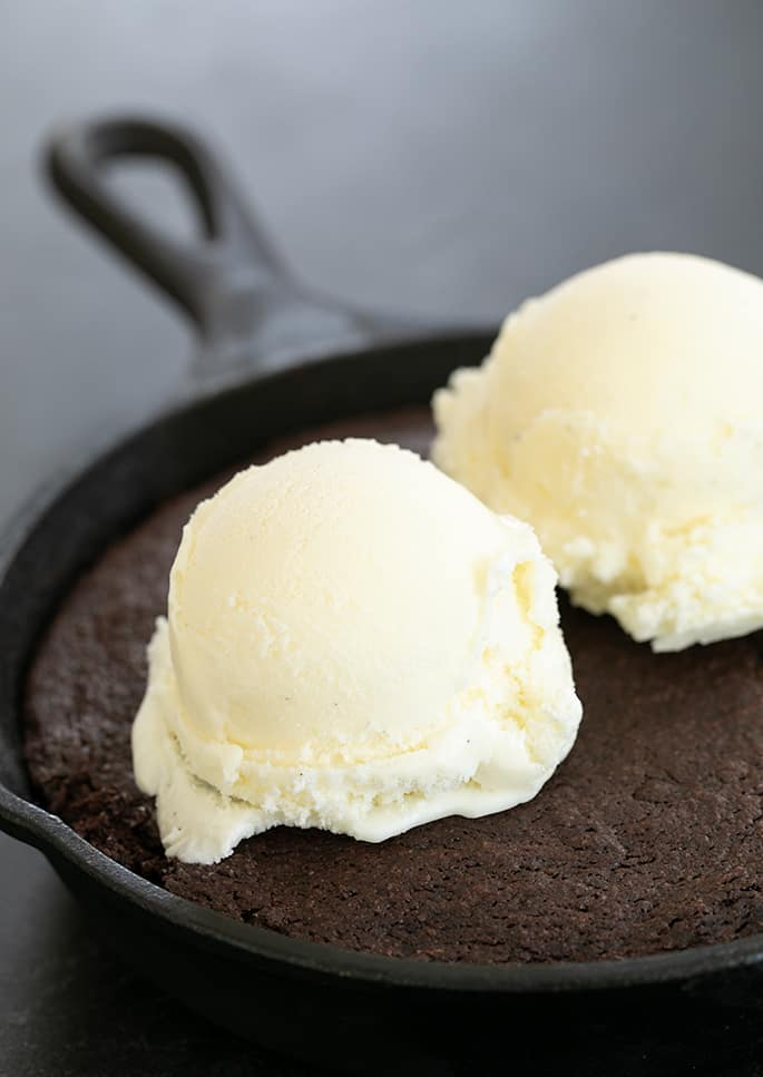 Skillet brownie baked in skillet with two scoops of vanilla ice cream