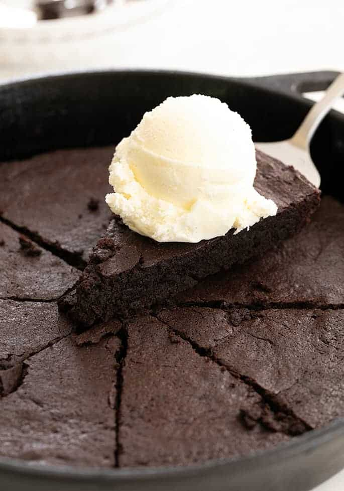 Skillet brownie slice on a spatula with a scoop of vanilla ice cream