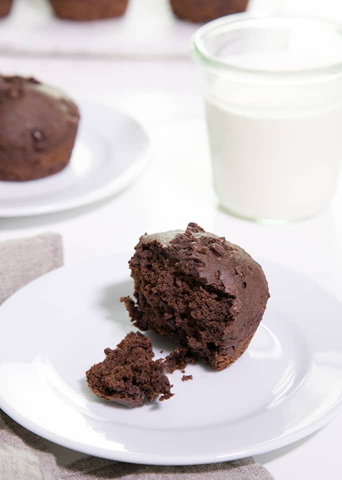 A chocolate muffin on a white plate with white jar and another plate of a chocolate muffin on white surface