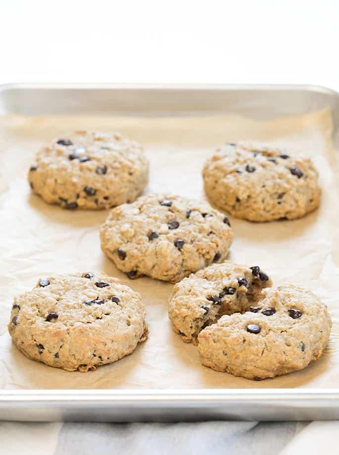 Oatmeal breakfast cookies baked on a tray, one cookie broken in half