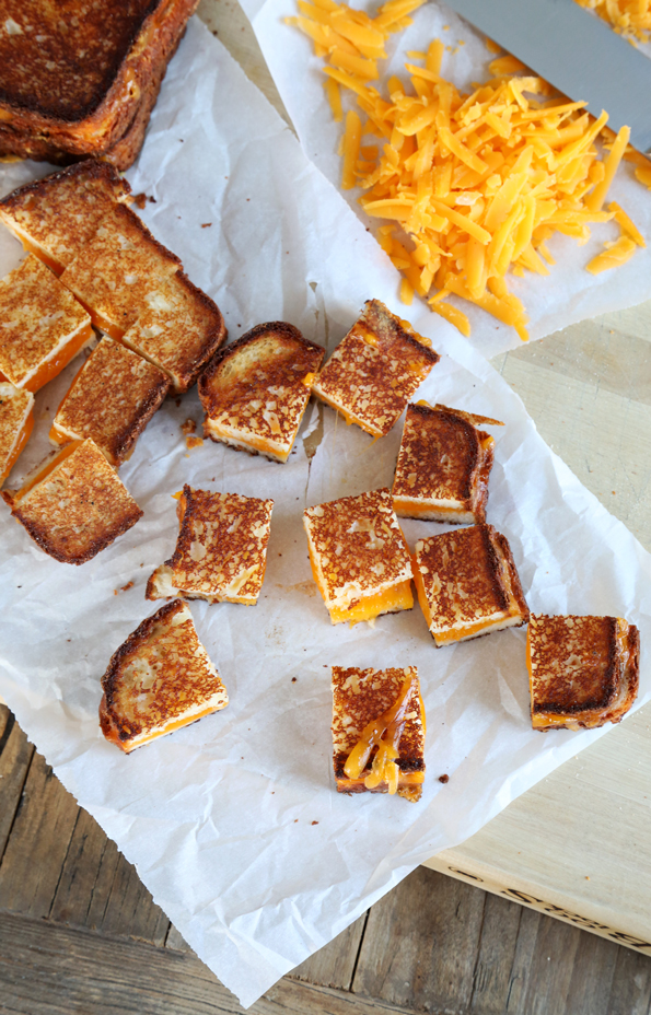 Overhead view of grilled cheese croutons on white surface