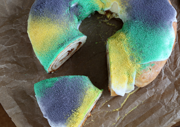 Overhead view of king cake on brown surface