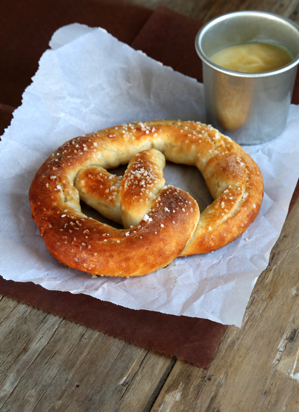 One baked gluten free soft pretzel on parchment on a table