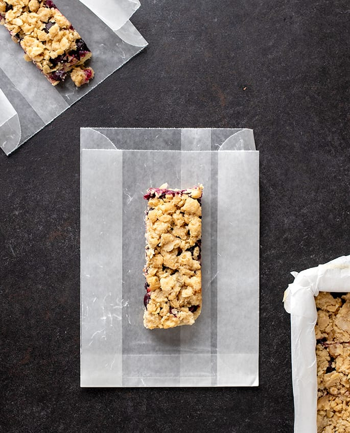 Overhead image of two bars on wax paper bags on black surface