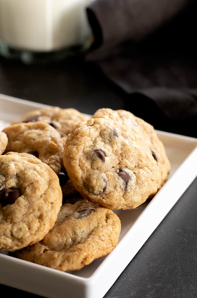 A corner of a white tray with small peanut butter oatmeal chocolate chip cookies on it
