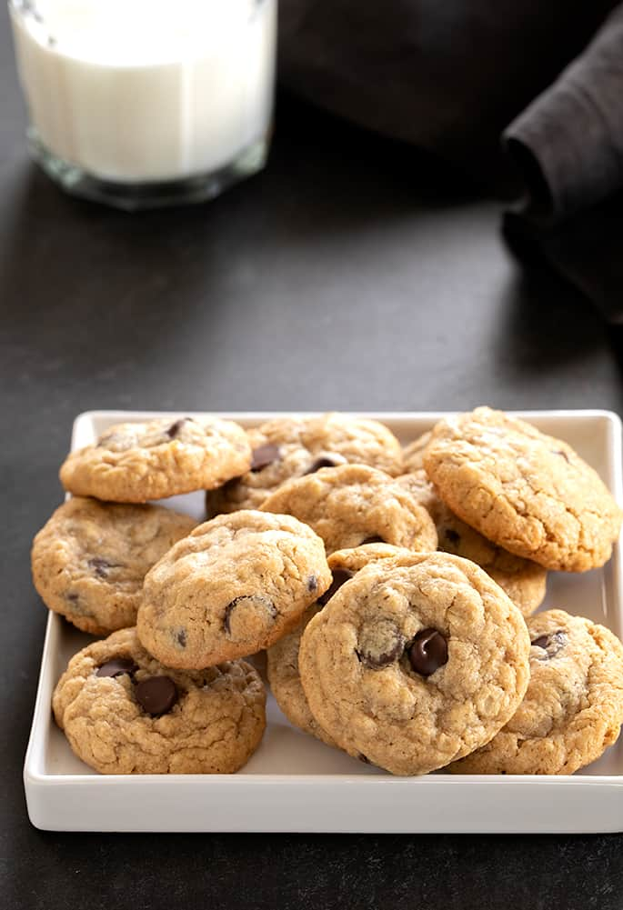 A pile of peanut butter oatmeal chocolate chip cookies on a square white tray