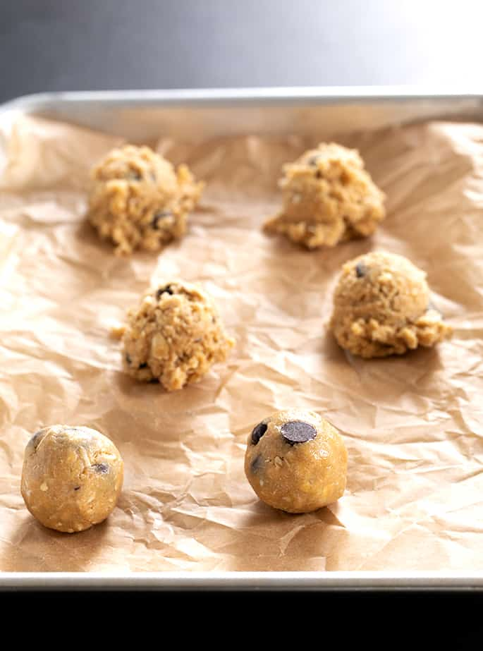 Raw peanut butter oatmeal chocolate chip cookies on a tray in balls