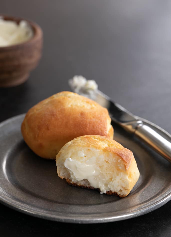 Gluten free Texas roadhouse rolls plated, showing the crumb inside of one roll.
