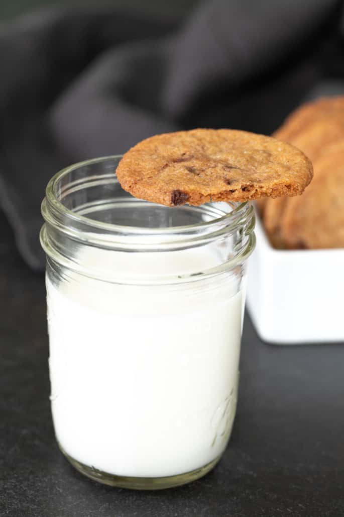 A glass of milk with one partially bitten gluten free cookie chip on top.