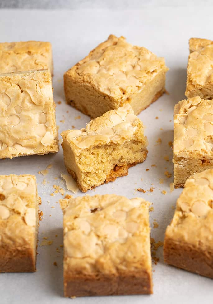 Cut square blondies on white paper with one broken in half in the center