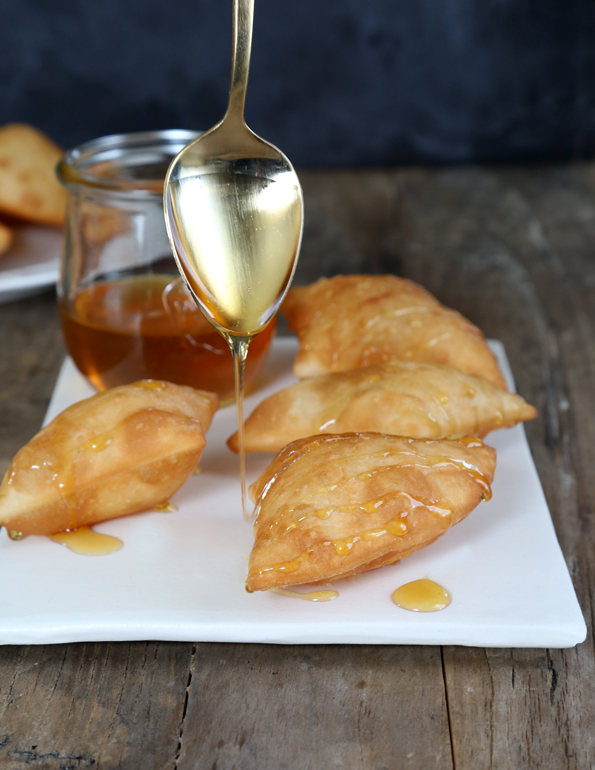 Sopapillas with honey being drizzled over them in a white plate