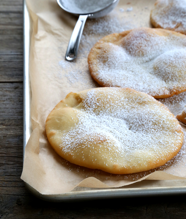 Fry bread with powdered sugar on metal tray