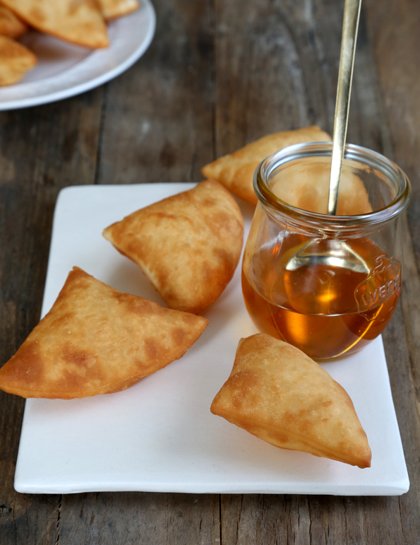 Sopapillas on white plate with jar of honey