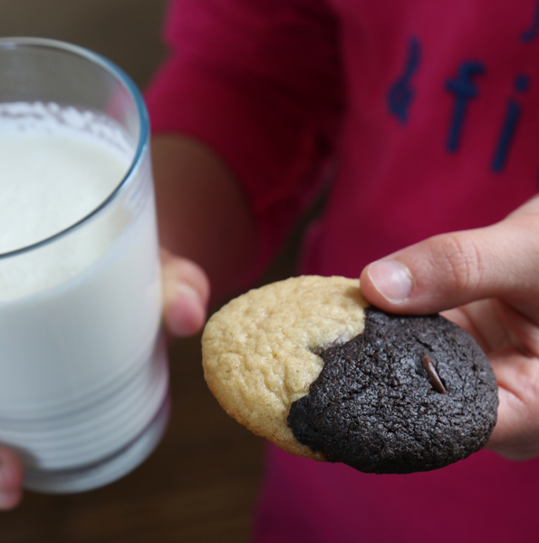 Person holding milk and a Half Brownie Half Chocolate Chip Cookie