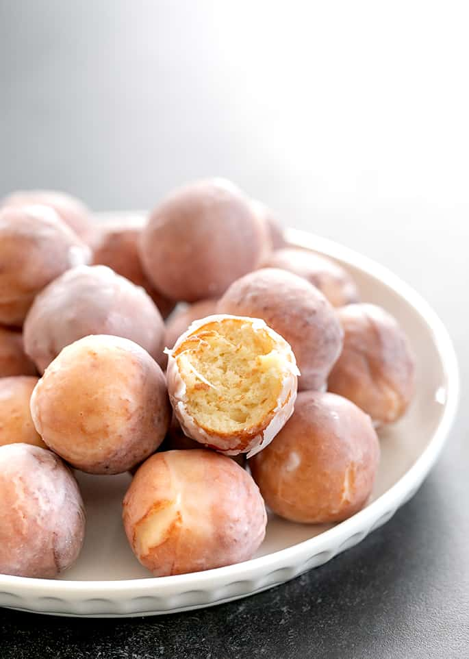 Donut holes being served with one bitten