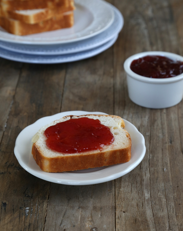 A close up of a Alice of bread with jam on white plate