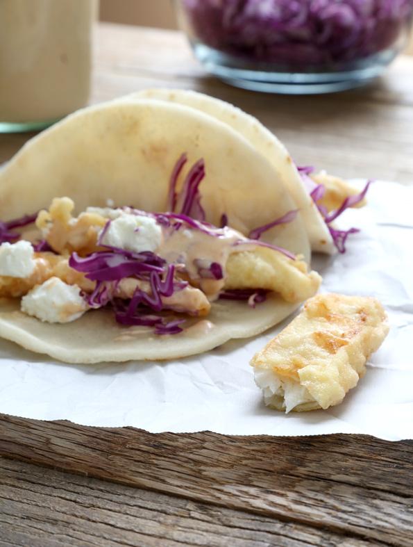 Close up of baja fish taco on white surface