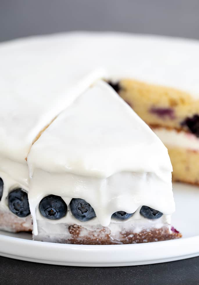 Gluten free lemon blueberry cake slice from behind, showing the glaze and fresh blueberries.