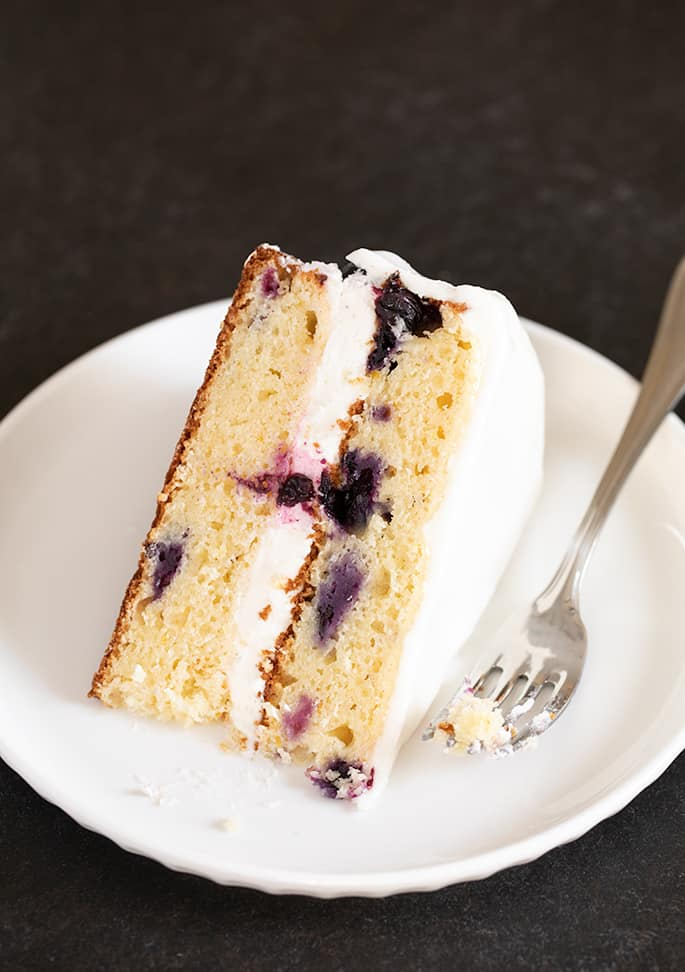 A piece of gluten free lemon blueberry cake with white frosting, on a plate.