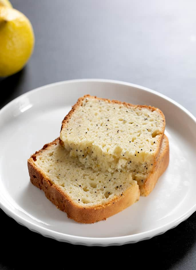 Two slices of gluten free lemon poppyseed bread on a plate, one broken in half to show moist and tender crumb inside.