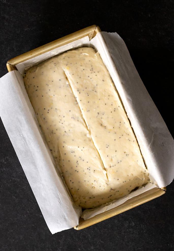 Gluten free lemon poppyseed bread shown raw in a loaf pan from overhead.