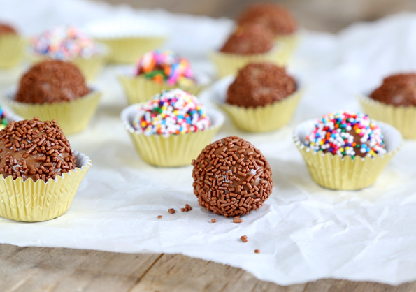 A close up of a Brigadeiro with chocolate sparkles on a white surface