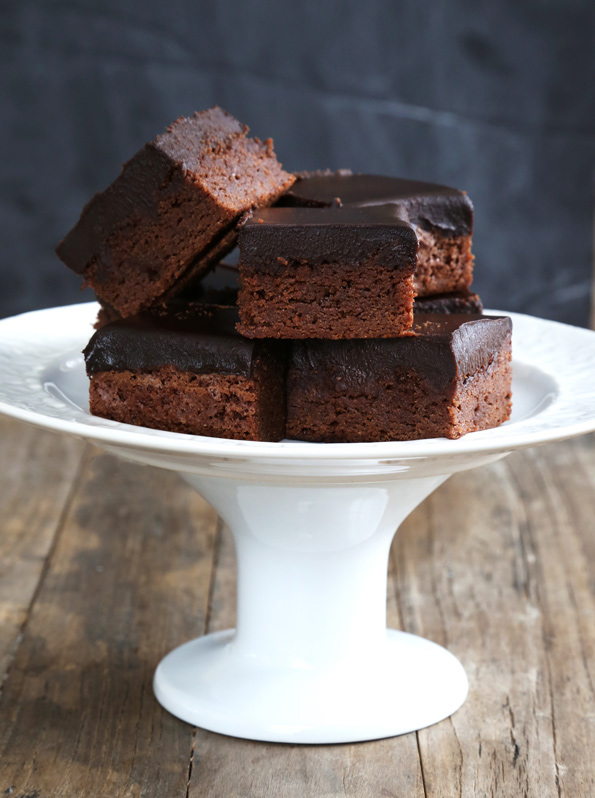 chocolate frosted brownies on white cake stand