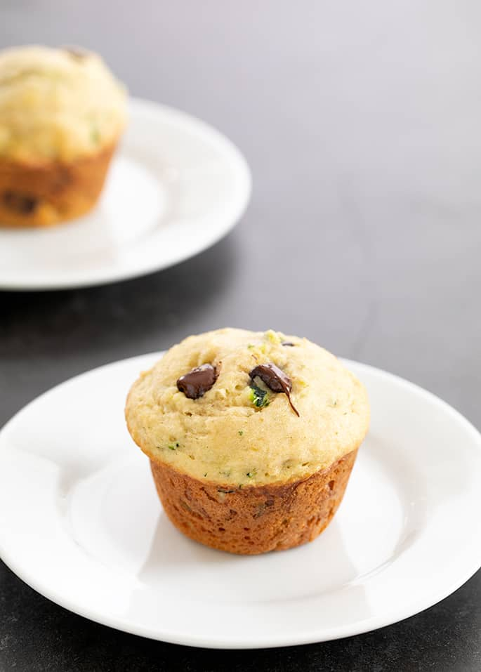 Two zucchini muffins each on a small white plate