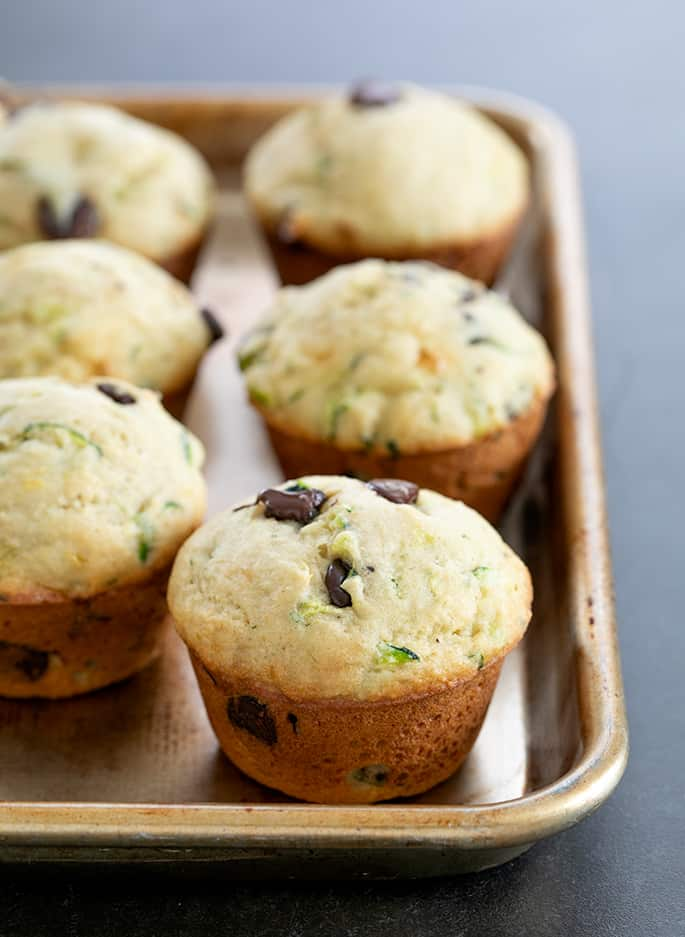 Whole baked zucchini muffins on a tray
