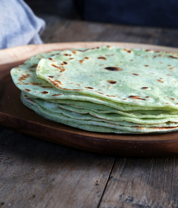 Side view of stack of zucchini flour tortillas on brown plate